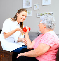 caregiver assiting the senior woman on physical therapy