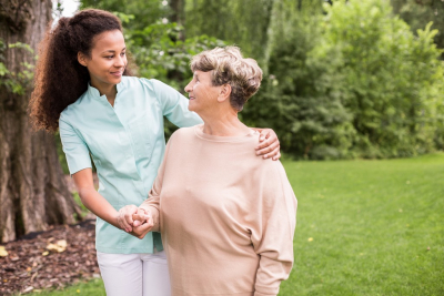 female caregiver and senior woman looking at each other outdoor
