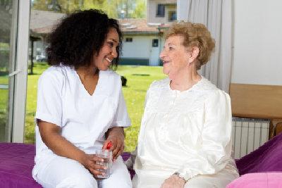 caregiver and senior woman talking indoor